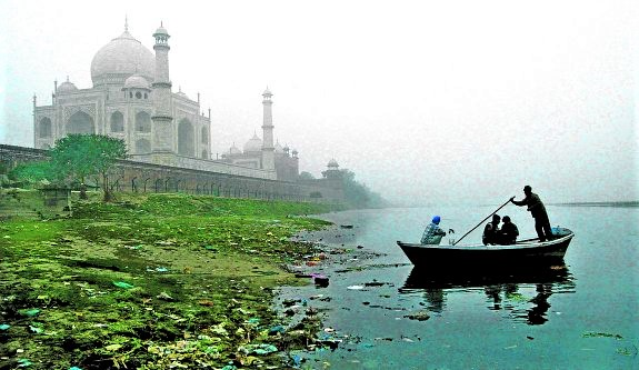 BOATMAN ROWS HIS BOAT ON A COLD AND FOGGY MORNING IN AGRA